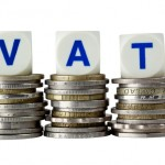 Stacks of coins with the letters VAT isolated on white background